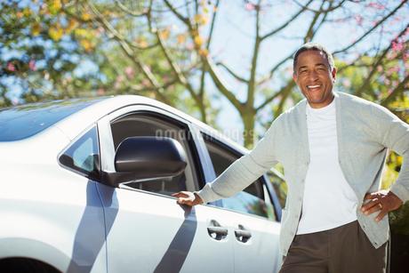 Portrait of confident senior man leaning against carの写真素材 [FYI02186481]
