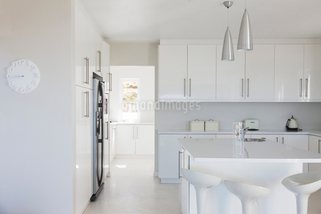 Modern white and clean kitchen interior with stools at counterの写真素材 [FYI02186488]