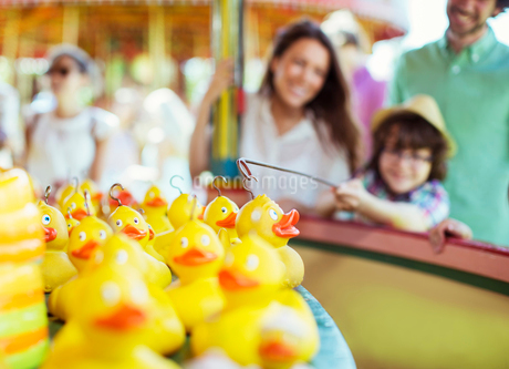 Boy trying to catch rubber duck on fishing game in amusement parkの写真素材 [FYI02186491]