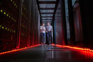 IT technicians talking and walking in dark server roomの写真素材 [FYI02186510]