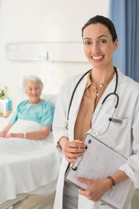 Portrait of smiling doctor with senior patient in backgroundの写真素材 [FYI02186526]