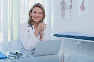 Portrait of smiling female doctor sitting at desk with laptopの写真素材 [FYI02186527]