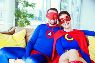 Superhero couple smiling on living room sofaの写真素材 [FYI02186553]