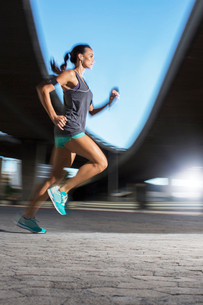 Woman running through city streetsの写真素材 [FYI02186580]