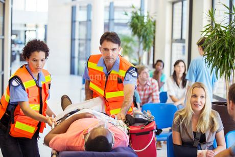 Paramedics wheeling patient in hospitalの写真素材 [FYI02186600]
