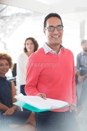 Portrait of smiling businessman wearing glasses and pink sweatshirt holding documents, office team iの写真素材 [FYI02186631]