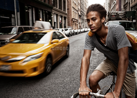 Man riding bicycle on city streetの写真素材 [FYI02186639]