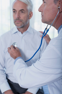 Doctor examining patient with stethoscope in officeの写真素材 [FYI02186657]