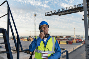 Worker using walkie-talkie on cargo craneの写真素材 [FYI02186662]