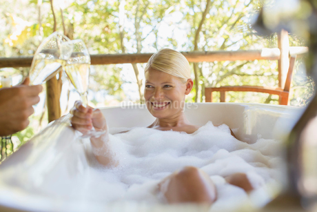 Couple toasting each other in bubble bathsの写真素材 [FYI02186663]