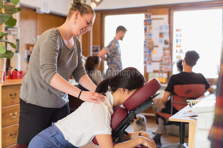 Creative businesswoman receiving massage from masseuse in officeの写真素材 [FYI02186670]