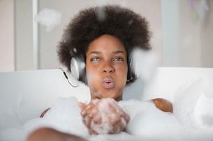 Woman listening to headphones in bathの写真素材 [FYI02186686]