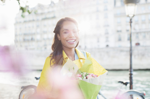 Woman with bouquet of flowers along Seine River, Paris, Franceの写真素材 [FYI02186698]