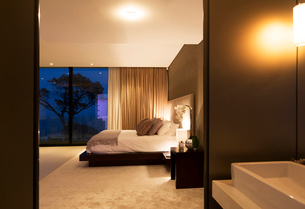 Beige and white bedroom with double bed seen from bathroom at nightの写真素材 [FYI02186701]