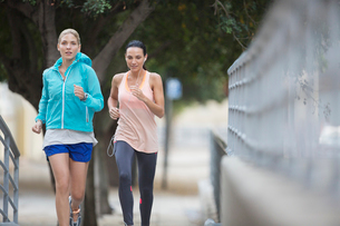 Women running through city streets togetherの写真素材 [FYI02186708]