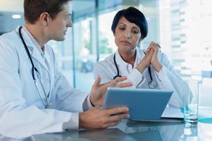 Doctors discussing patient's treatment at desk, using digital tabletの写真素材 [FYI02186711]