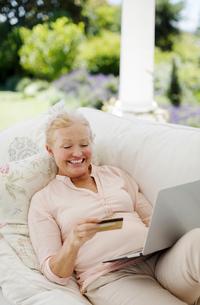 Senior woman shopping online on patio sofaの写真素材 [FYI02186731]