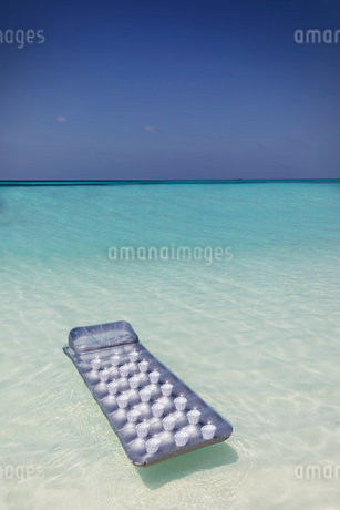 Inflatable raft floating on tranquil blue tropical oceanの写真素材 [FYI02186740]