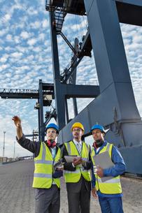 Businessmen and worker talking near cargo craneの写真素材 [FYI02186749]