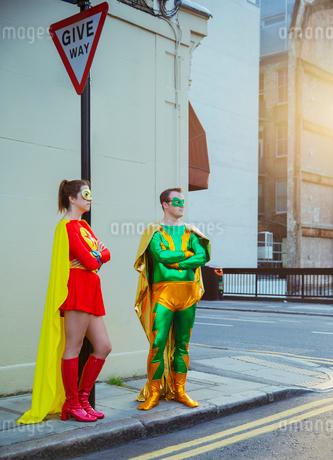 Superhero couple waiting at corner on city sidewalkの写真素材 [FYI02186764]