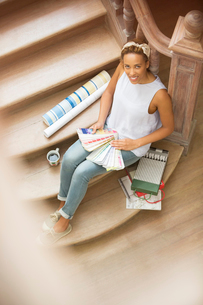 Woman sitting on stairs looking through color swatchesの写真素材 [FYI02186770]