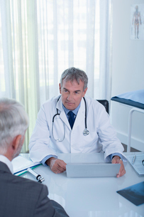 Mature doctor with laptop and man sitting at desk in officeの写真素材 [FYI02186772]