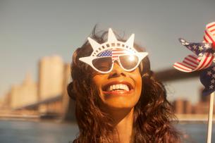 Woman with novelty sunglasses and pinwheel by urban bridgeの写真素材 [FYI02186775]