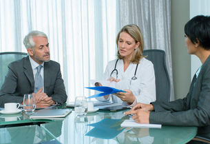 Female doctor, man and woman talking at table in conference roomの写真素材 [FYI02186780]