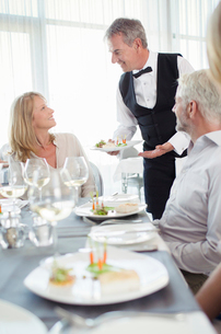 Waiter serving fancy dish to woman sitting at restaurant tableの写真素材 [FYI02186800]