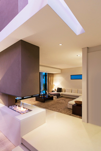 View of spacious modern living room with fireplace during nightの写真素材 [FYI02186828]