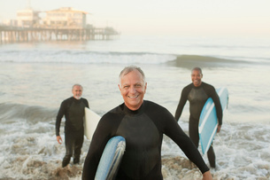 Older surfers carrying boards on beachの写真素材 [FYI02186831]