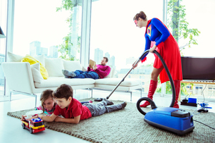 Superhero vacuuming around family in living roomの写真素材 [FYI02186843]