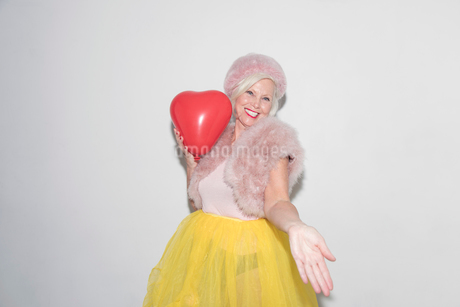 Portrait carefree, playful senior woman with heart-shape balloonの写真素材 [FYI02186847]