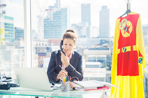 Businesswoman working with superhero costume hanging in officeの写真素材 [FYI02186879]