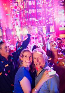 Confetti falling on smiling mature people dancing in nightclubの写真素材 [FYI02186897]
