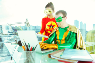 Superheroes working with laptop in officeの写真素材 [FYI02186900]