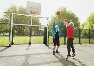 Active senior men friends playing basketball in sunny parkの写真素材 [FYI02186905]