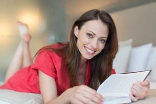 Portrait of smiling woman lying on bed and reading bookの写真素材 [FYI02186906]