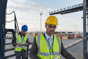 Businessman smiling near cargo craneの写真素材 [FYI02186907]