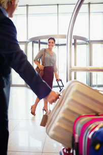Man taking suitcase from luggage cart in hotel lobby, smiling woman in backgroundの写真素材 [FYI02186917]