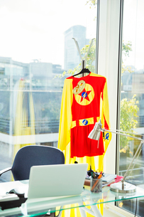 Superhero costume hanging in business officeの写真素材 [FYI02186919]