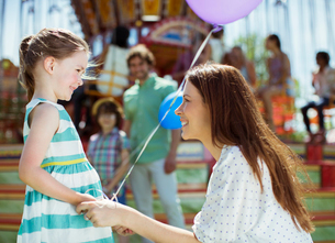 Mother and girl with balloon looking at each other in amusement parkの写真素材 [FYI02186929]