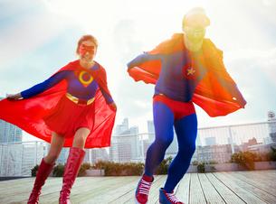 Superheroes running on city rooftopの写真素材 [FYI02186930]