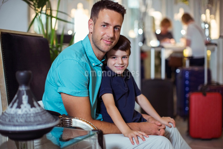 Portrait of man with son sitting in hotel lobbyの写真素材 [FYI02186939]