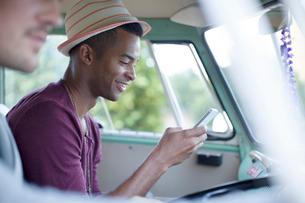 Man using cell phone in camper vanの写真素材 [FYI02186988]