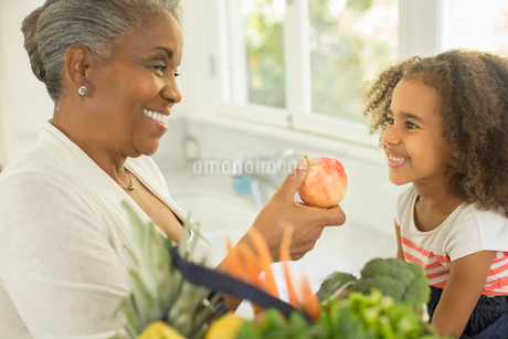 Happy grandmother giving apple to granddaughter in kitchenの写真素材 [FYI02186991]