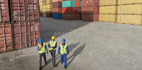Businessmen and worker walking near cargo containersの写真素材 [FYI02187000]