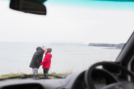 Affectionate couple kissing outside motor home on cliff overlooking oceanの写真素材 [FYI02187019]