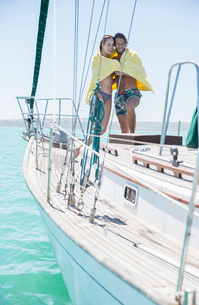 Couple sharing towel in boat on waterの写真素材 [FYI02187029]