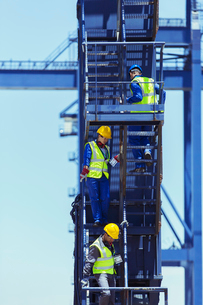 Businessman and workers climbing stairs on cargo craneの写真素材 [FYI02187034]